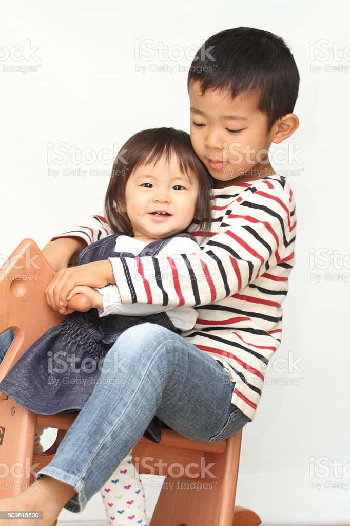 Japanese brother and sister playing with rocking horse stock photo