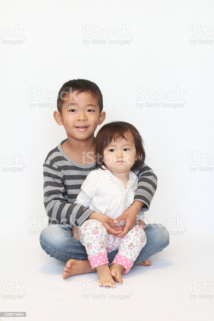 Japanese brother and sister sitting on his knee stock photo