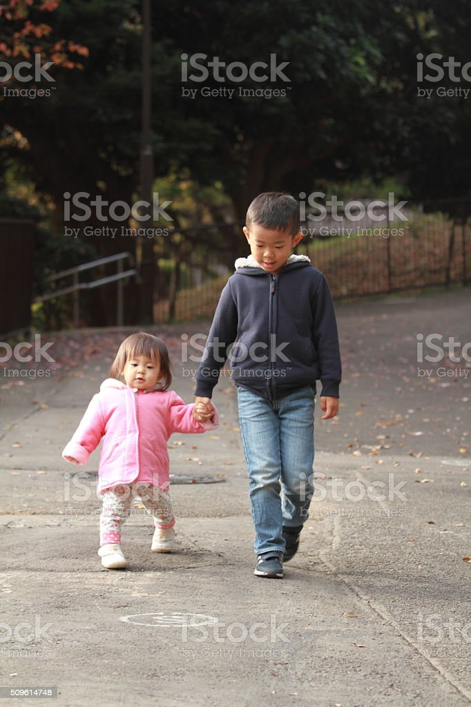 Japanese brother and sister taking a walk stock photo