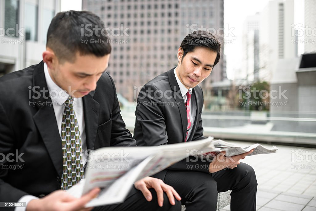 japanese Business man reading the newspaper on the downtown stock photo