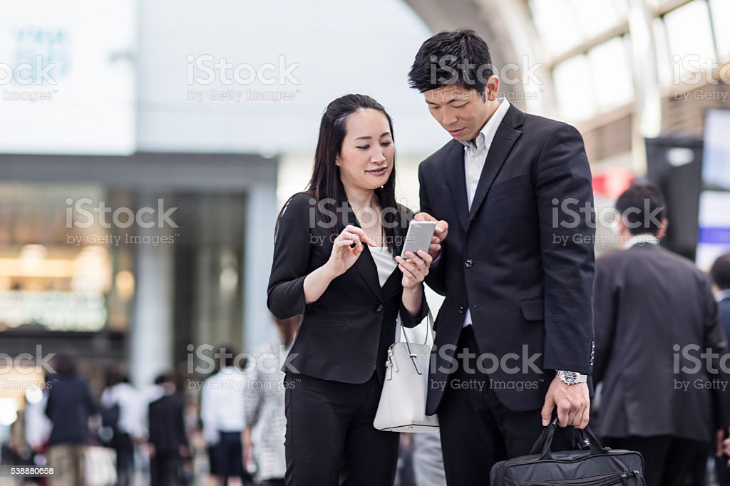 Japanese business people looking at the mobile phone at station stock photo
