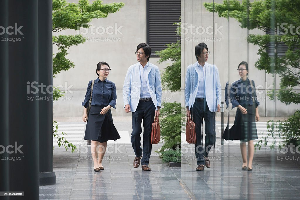 Japanese business people reflected in office building glass stock photo