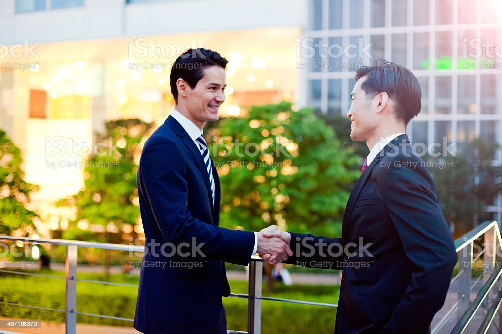 Japanese business people warmly greating. stock photo