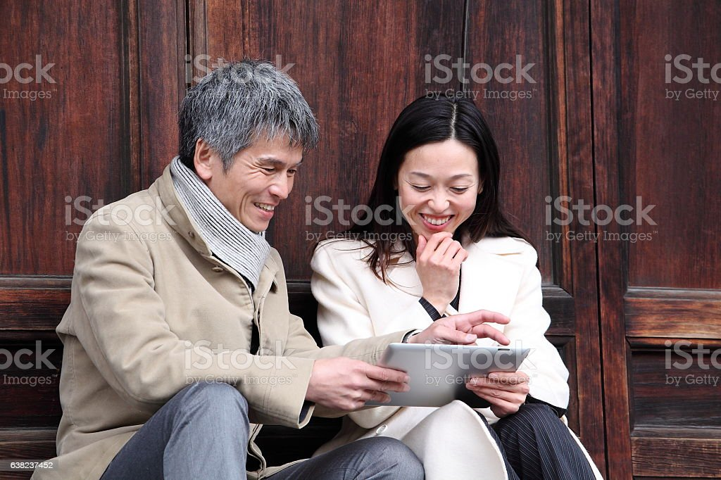 Japanese business persons looking tablet PC at Tofuku-ji Temple, Kyoto stock photo