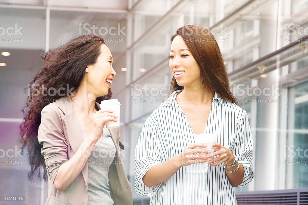 Japanese business woman laughs with assistant on coffee break stock photo