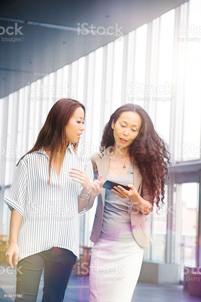 Japanese business woman share info with assistant on mobile phone stock photo