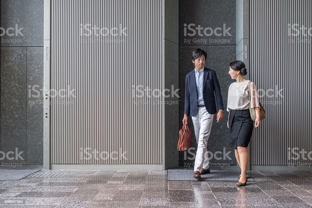 Japanese Businessman and Businesswoman Exiting Elevator in Modern Office Building stock photo