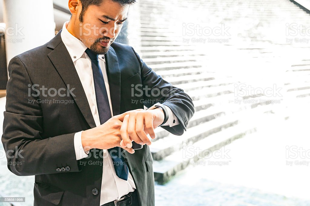 Japanese businessman checking his smart watch stock photo