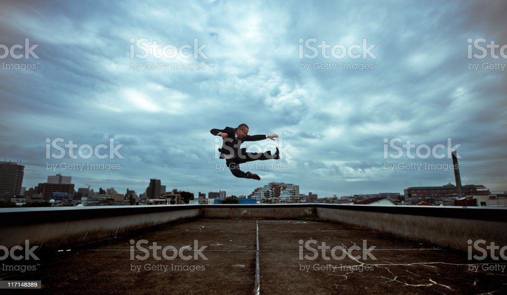 Japanese businessman doing a flying kick stock photo