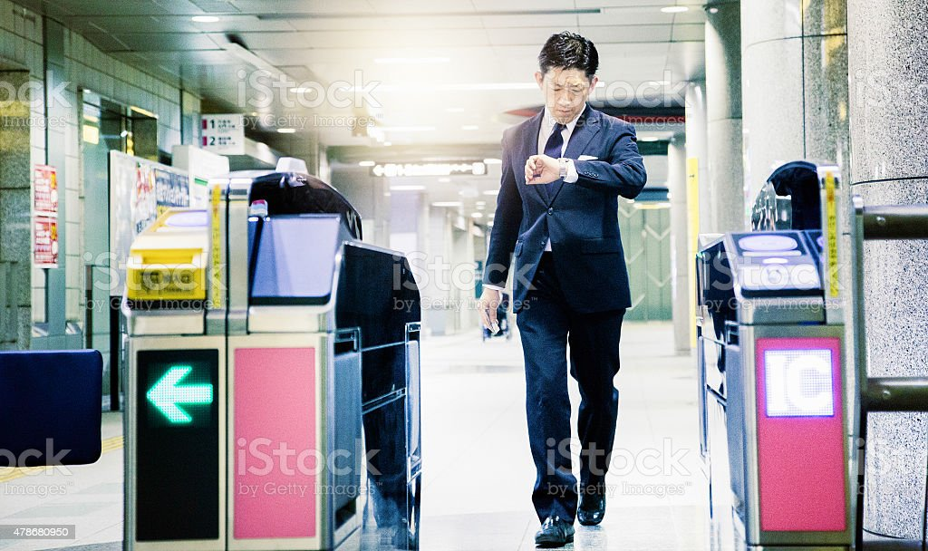 Japanese businessman in a hurry exits subway looking at watch stock photo