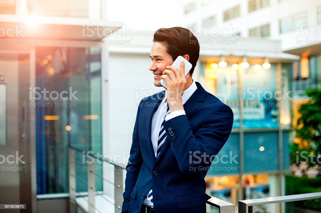 Japanese businessman on the phone outdoors, Tokyo stock photo