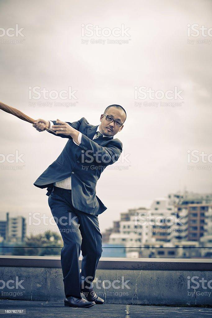 Japanese businessman playing baseball with an umbrella stock photo