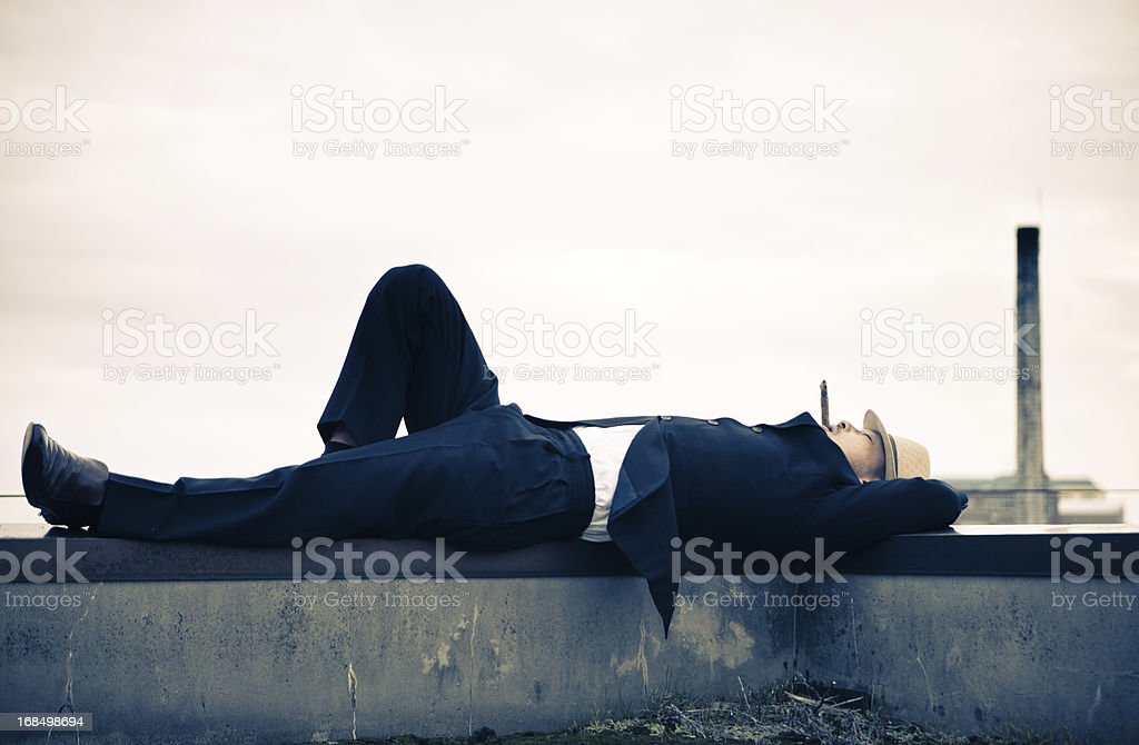 Japanese Businessman smoking a cigar on rooftop in Tokyo royalty-free stock photo