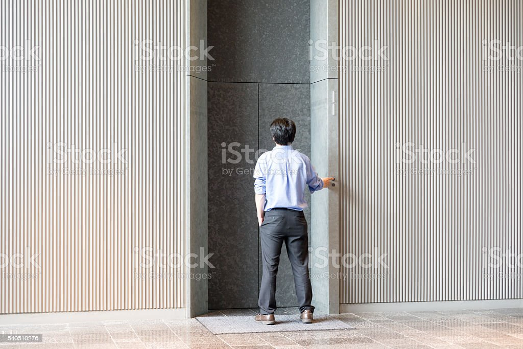 Japanese businessman standing and waiting for elevator stock photo