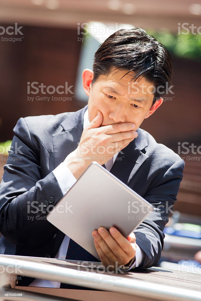 Japanese businessman stricken with grief guilt fear looking at tablet stock photo