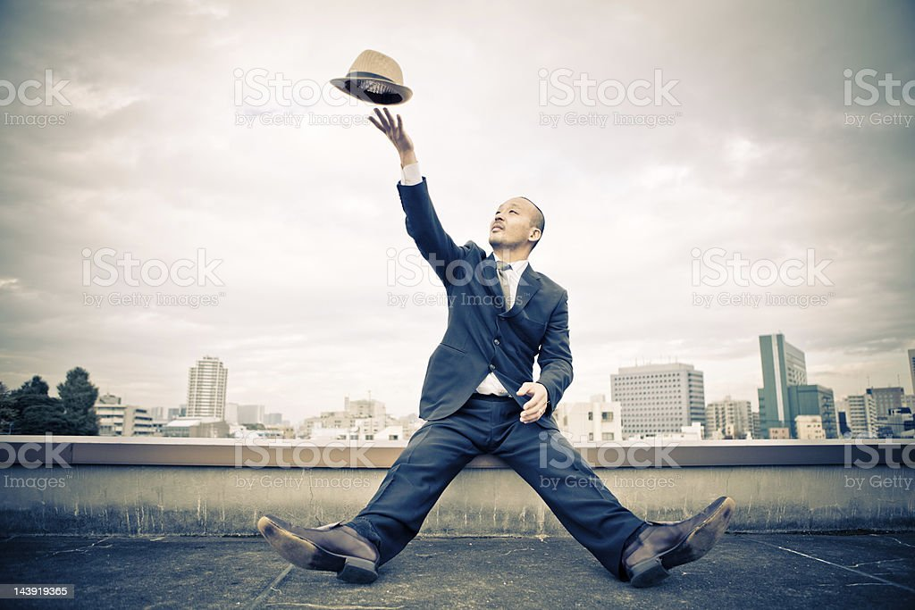 Japanese businessman tossing his hat in the air stock photo