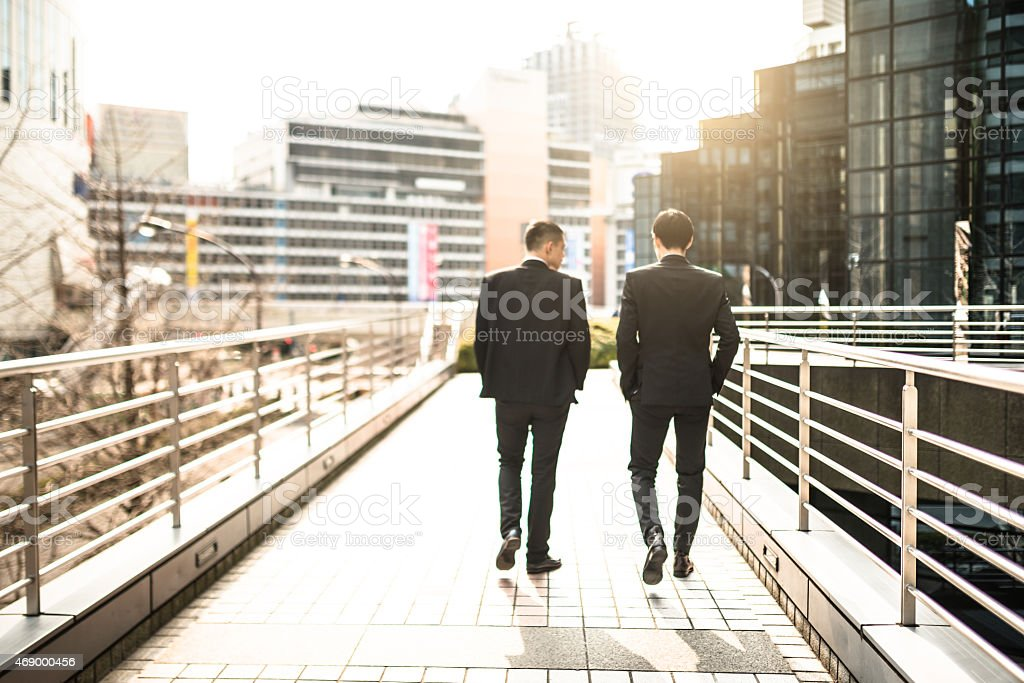 japanese businessman walking and talking on the city stock photo