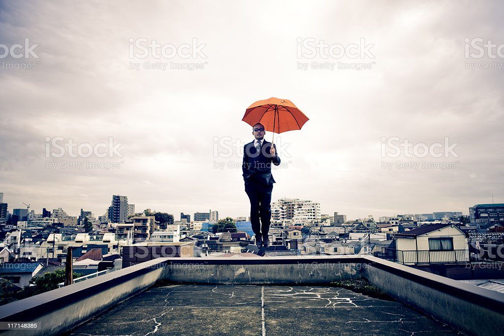 Japanese businessman with umbrella floating above Tokyo stock photo