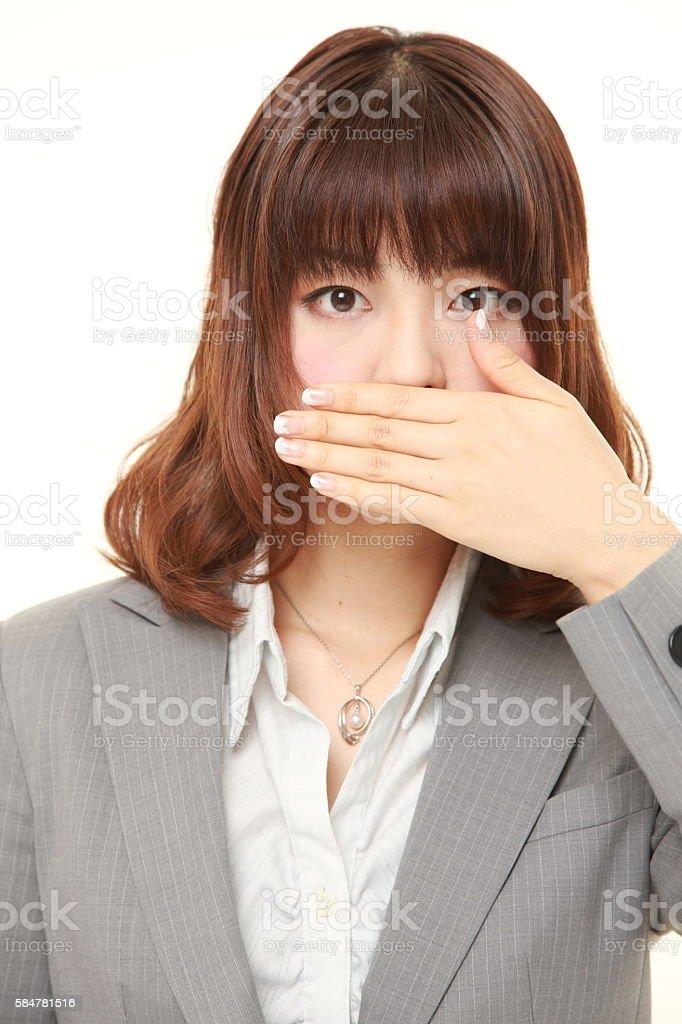 Japanese businesswoman making the speak no evil gesture stock photo