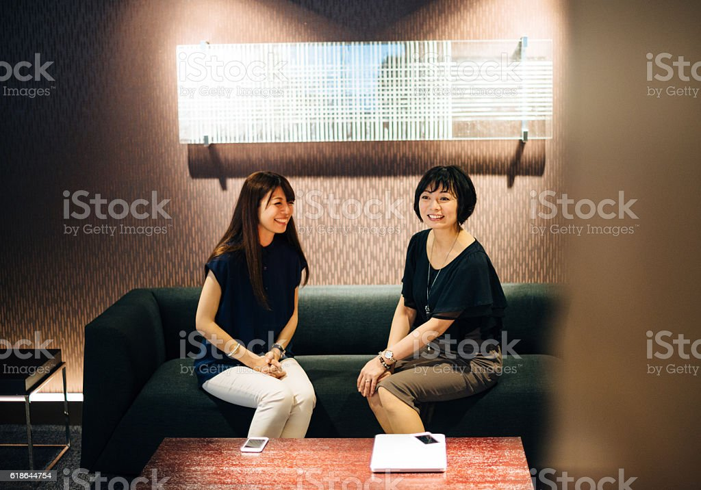 Japanese businesswomen discuss and laugh stock photo