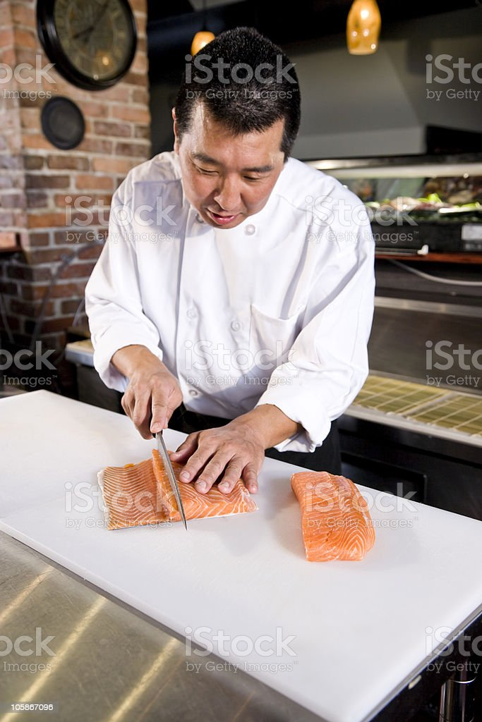 Japanese chef slicing raw fish for sushi royalty-free stock photo