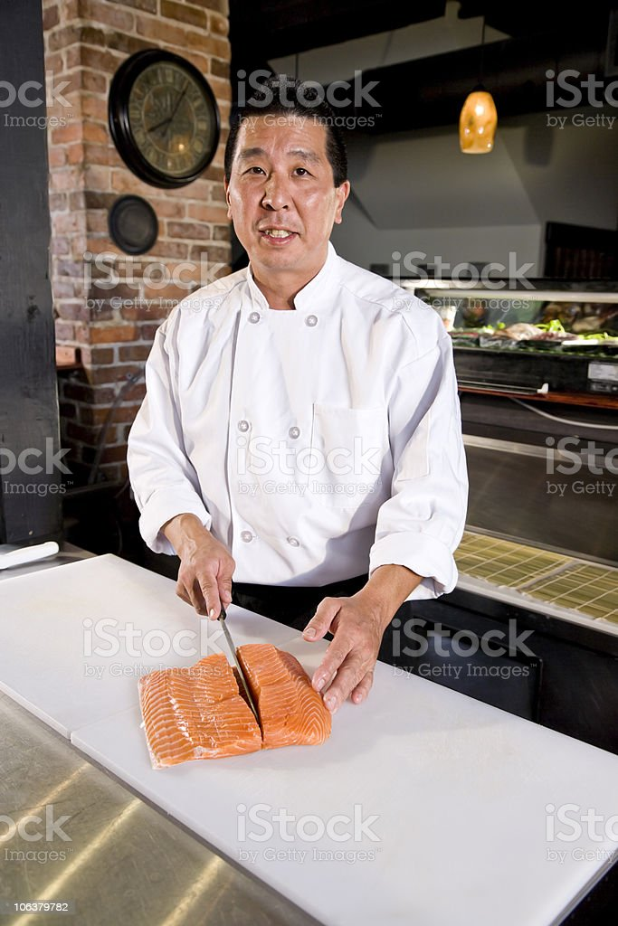 Japanese chef slicing raw fish for sushi royalty-free stock photo