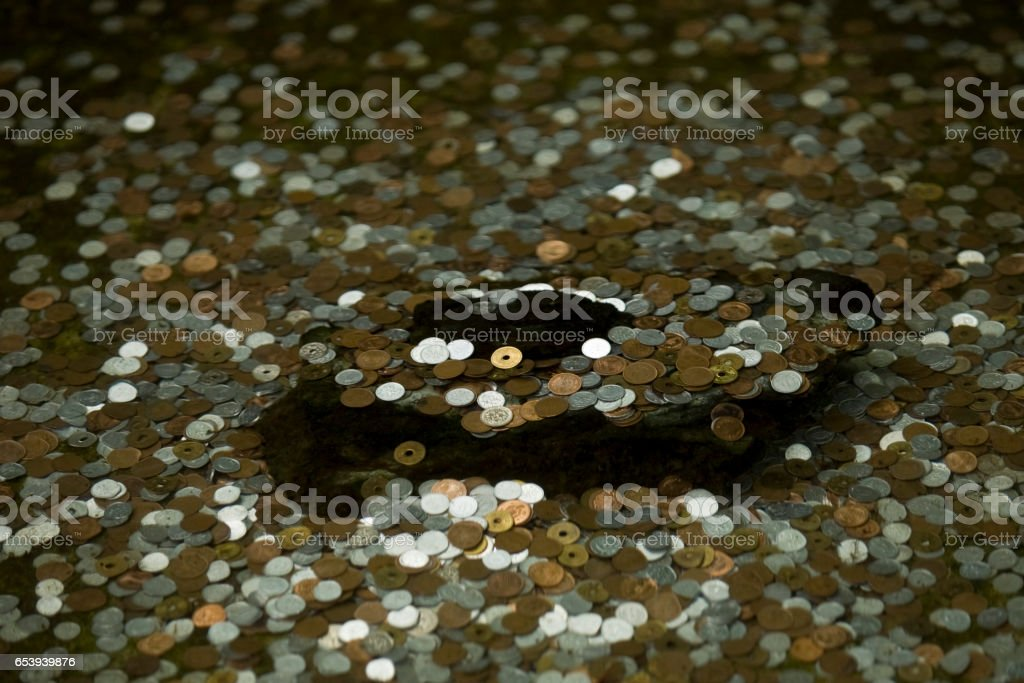 Japanese coins thrown for memory into pond. stock photo