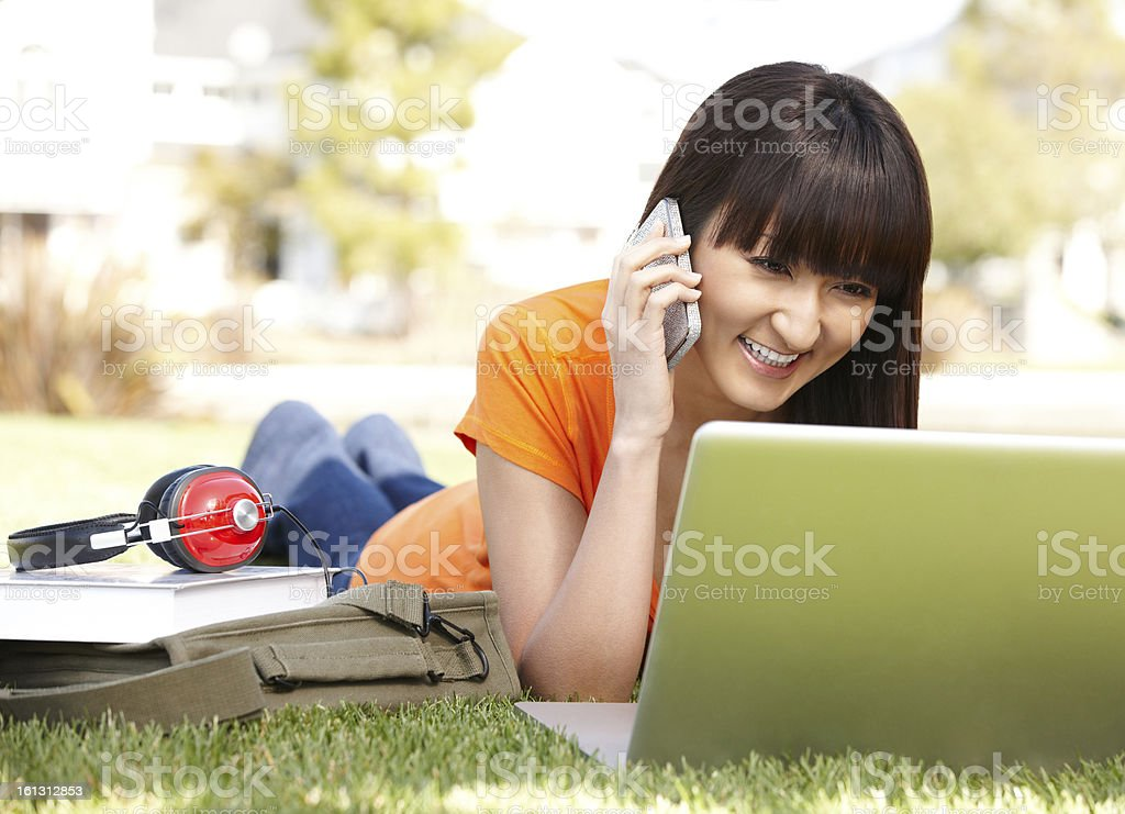 Japanese college student on phone using computer outdoors royalty-free stock photo