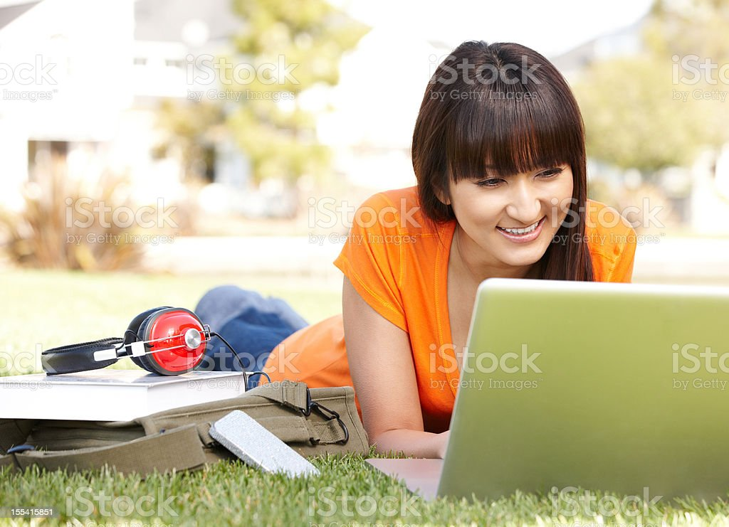 Japanese college student studying on computer in grass royalty-free stock photo