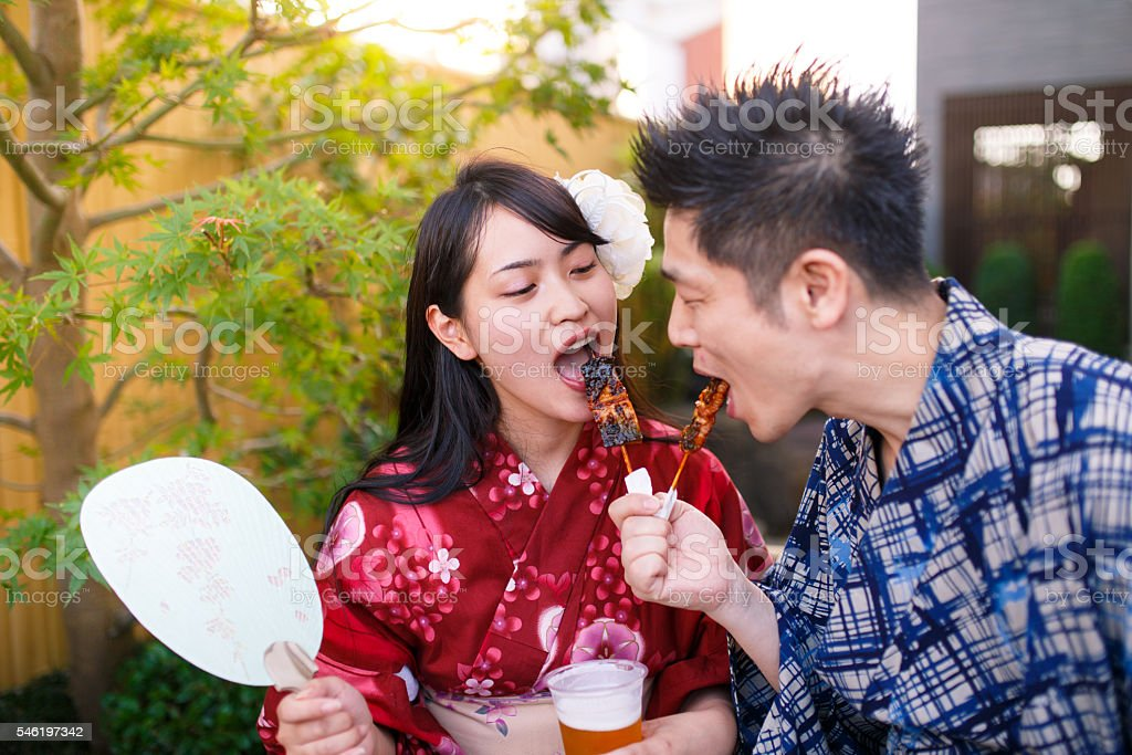 Japanese couple eating Yakitori at festival stock photo