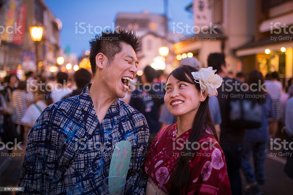 Japanese couple laughing with joy on street at festival stock photo