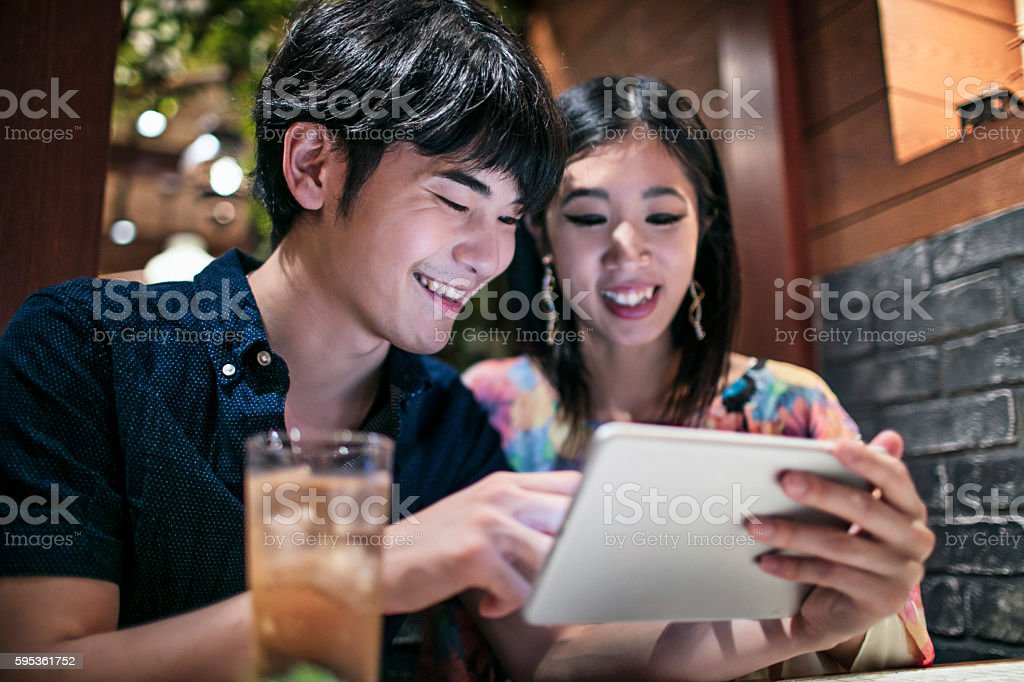 Japanese couple looking at a digital tablet in a cafeteria stock photo