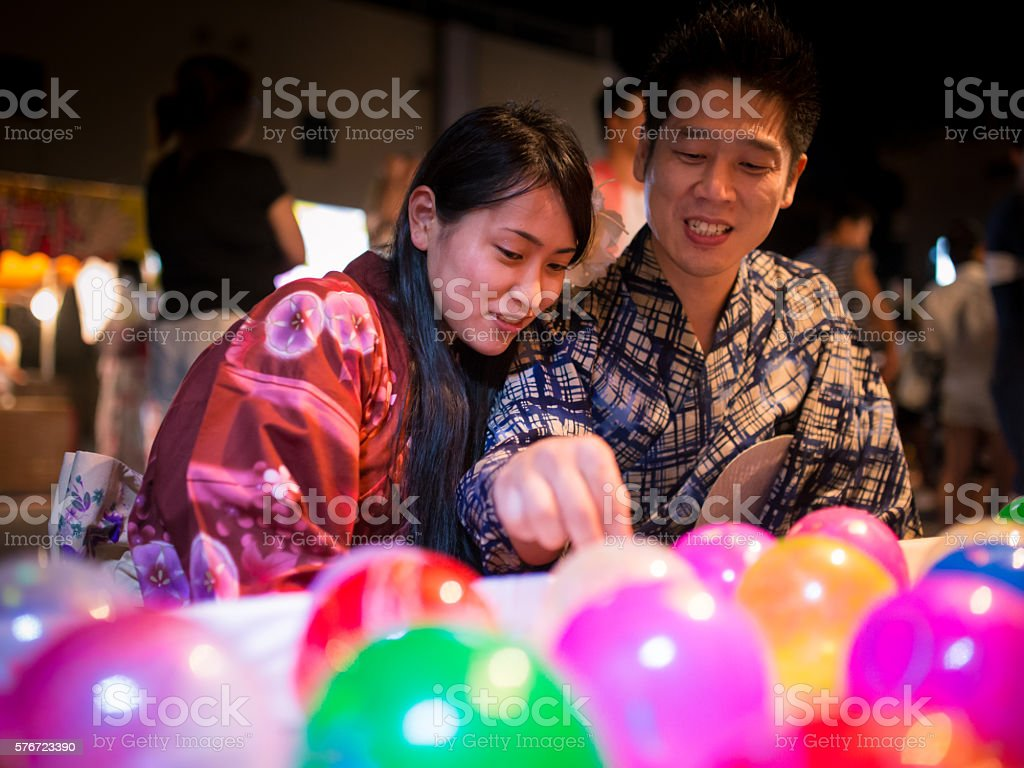 Japanese couple playing yo-yo fishing at festival stock photo