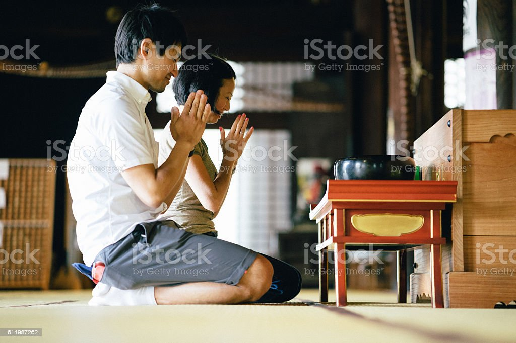 Japanese couple praying in a buddhist temple stock photo