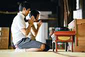 Japanese couple praying in a buddhist temple