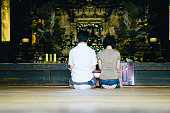 Japanese couple praying in a buddhist temple, rear view
