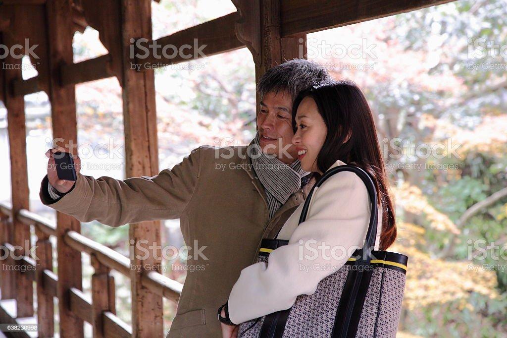 Japanese couple taking selfie on bridge at Tofuku-ji Temple, Kyoto stock photo