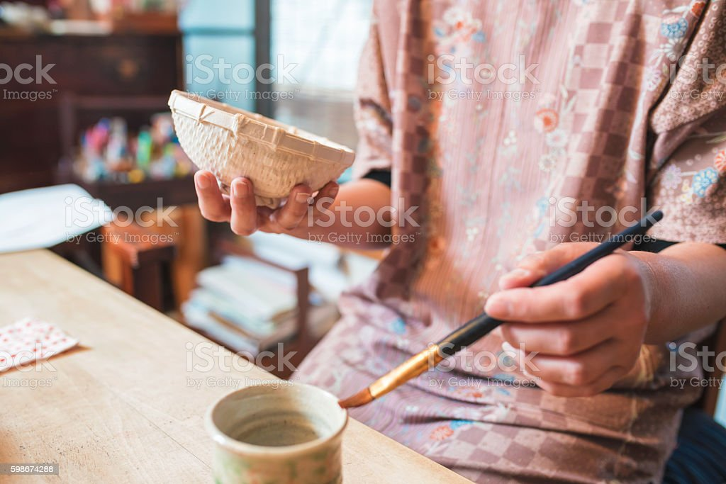 Japanese Craftsperson painting a paper bowl stock photo