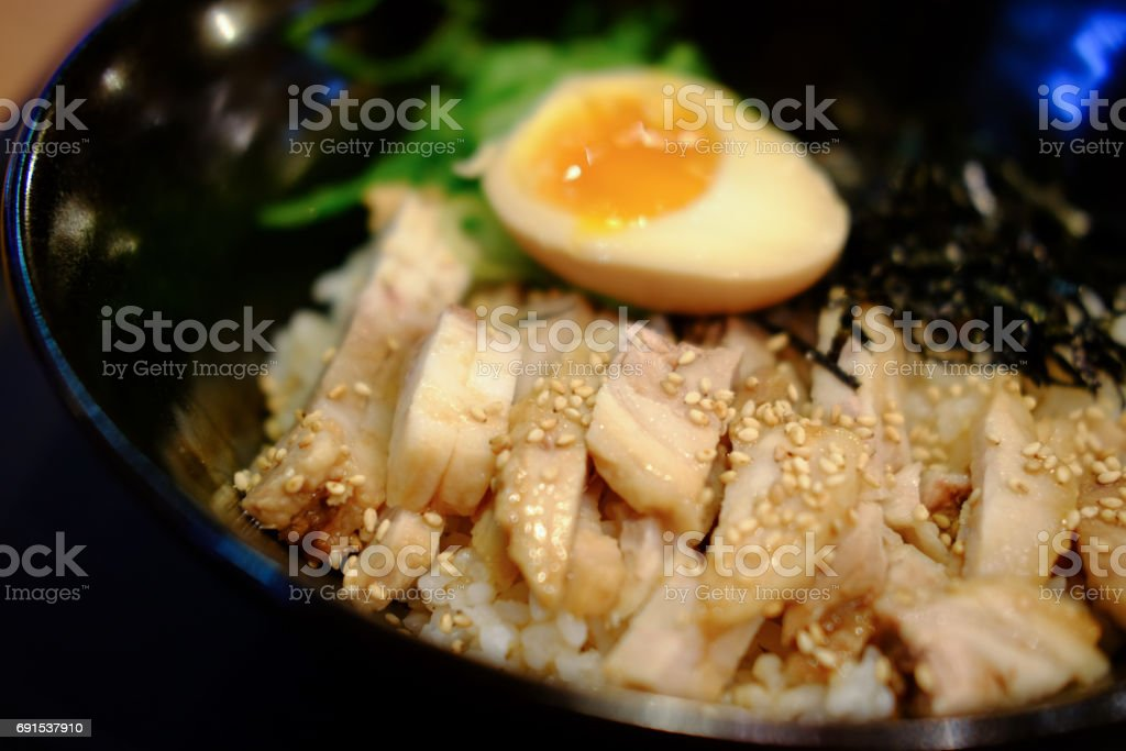 Japanese cuisine rice with soft boil eggs and fried pork topped white sesame stock photo