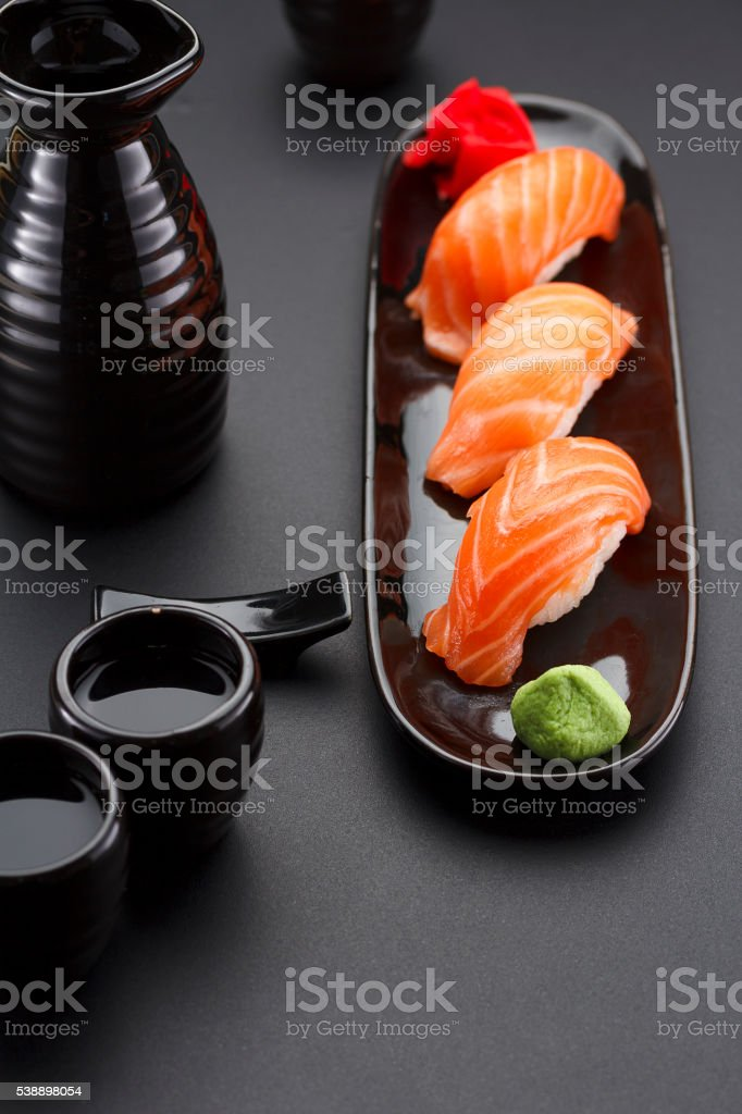 Japanese cuisine. Sushi roll with soy sauce over black background. stock photo