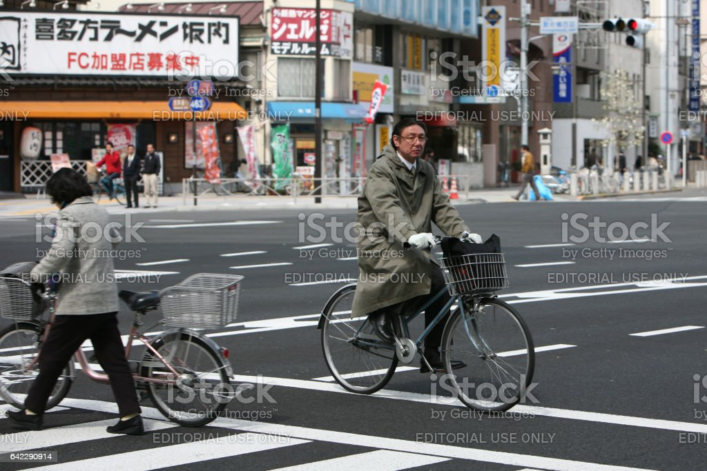 Japanese cyclists are crossing the street on a green traffic light stock photo