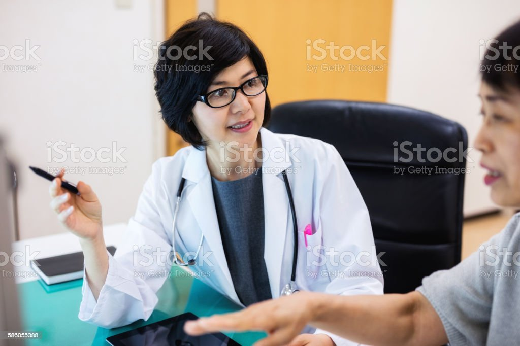 japanese Doctor talking to senior patient in hospital stock photo