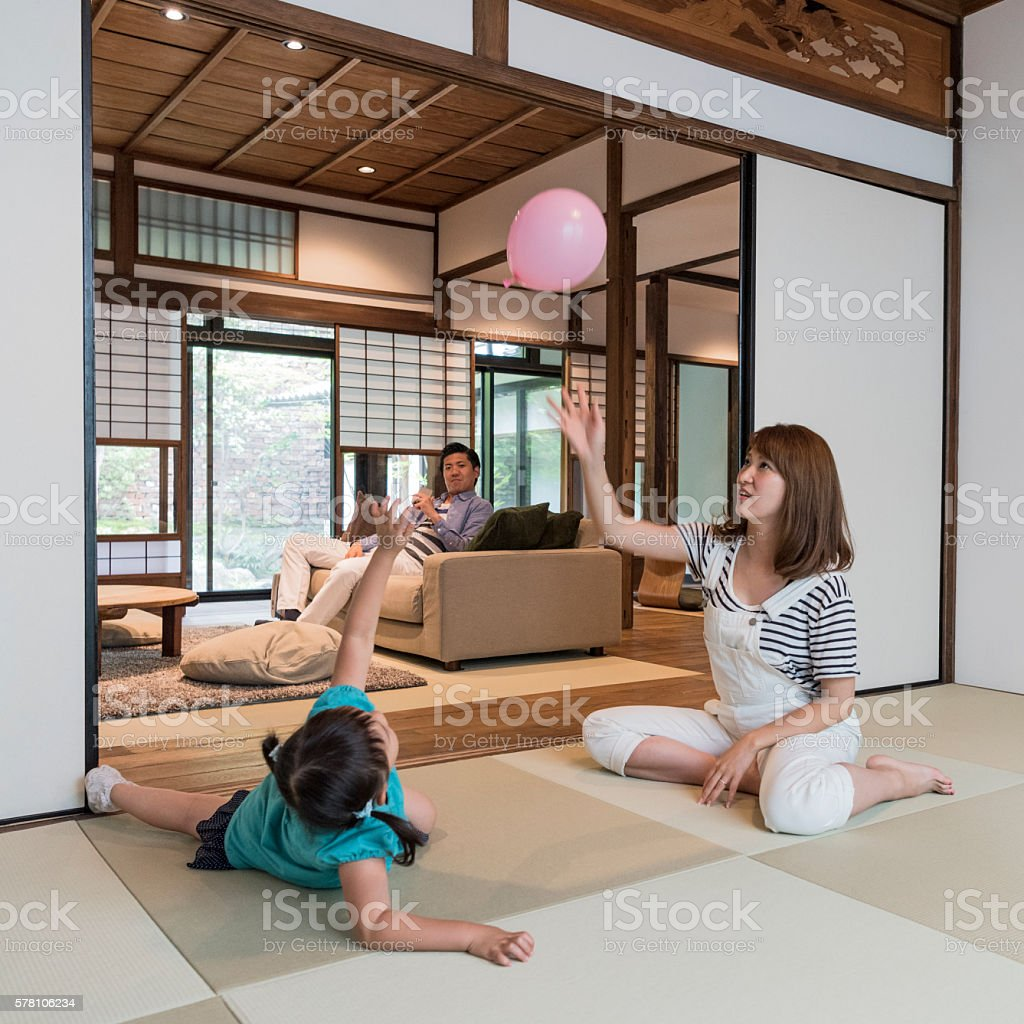 Japanese family at home, mother and daughter playing with balloon stock photo