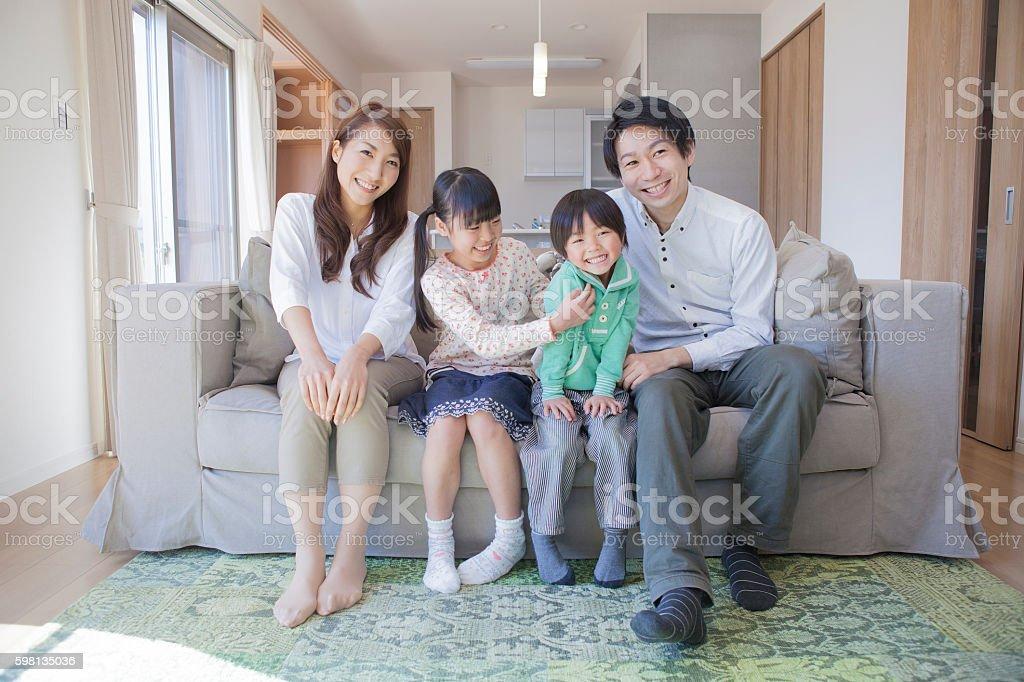 Japanese family sitting on sofa stock photo