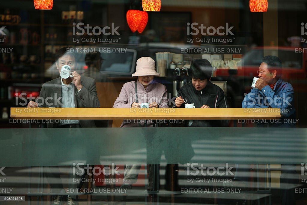 Japanese family, snacking in the Starbucks coffee house. stock photo