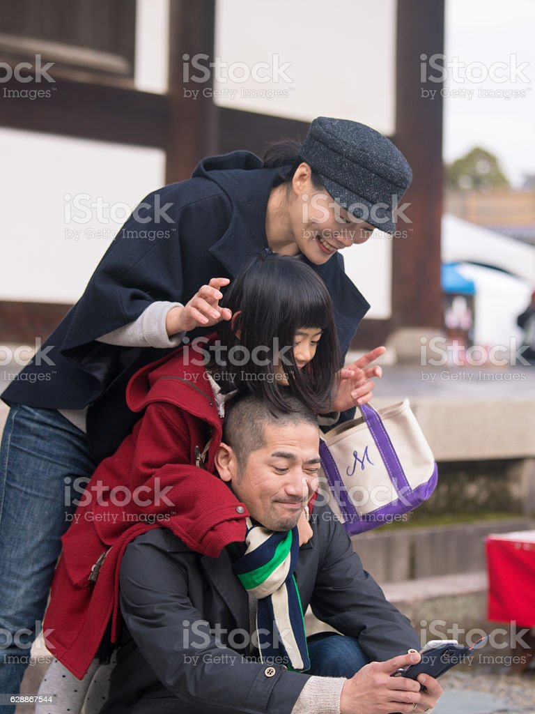Japanese family taking pictures in temple, Kyoto stock photo