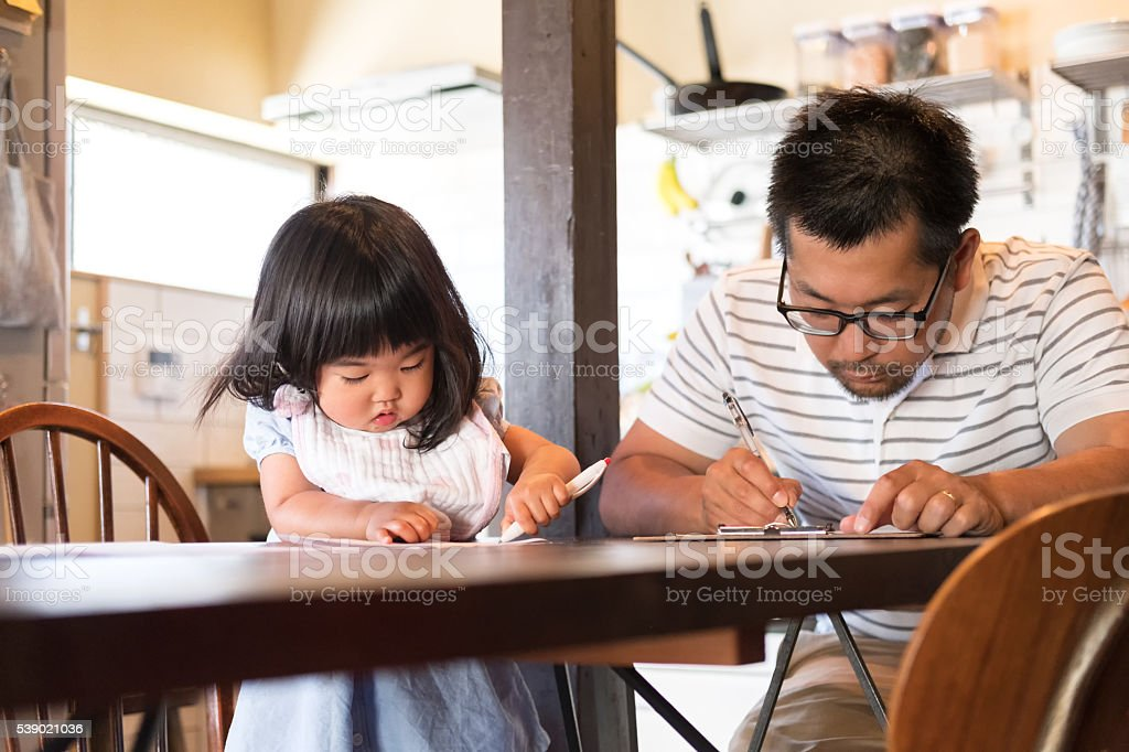 Japanese Father and Daughter Filling out Paperwork on Kitchen Table stock photo