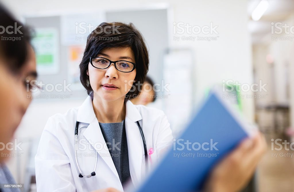 Japanese Female doctor talking to patient stock photo