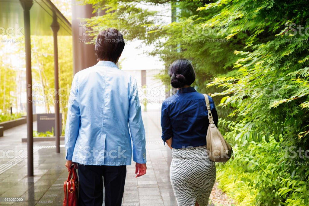 Japanese Female office worker with male colleague walking to work stock photo
