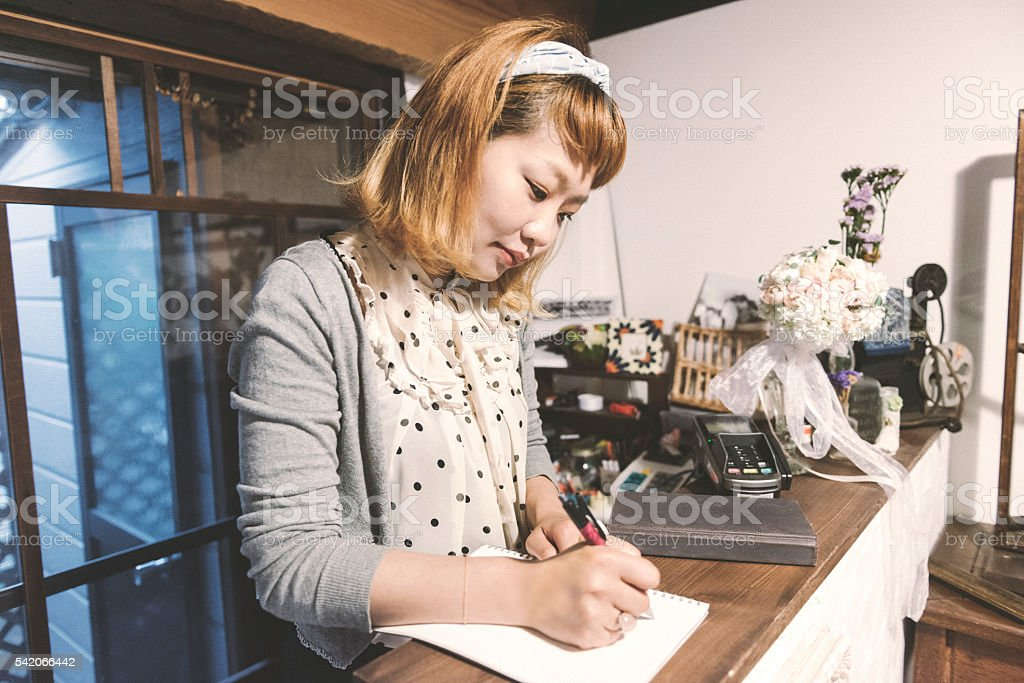 Japanese Female Small Business Owner Writing Daily Accounts Kyoto Japan stock photo